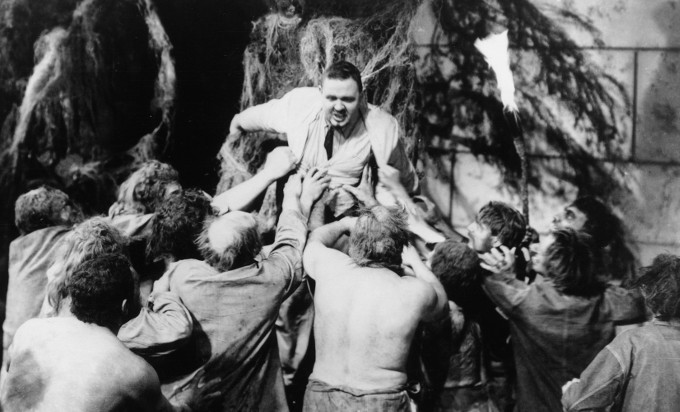 Charles Laughton as Dr. Moreau being attacked by his creations.